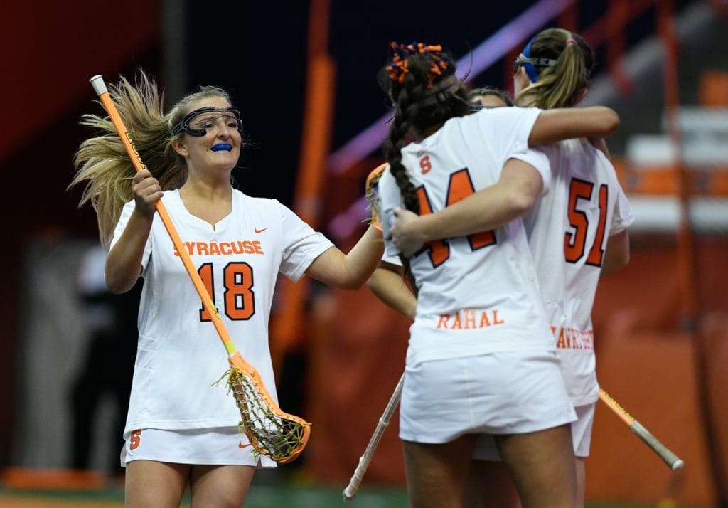 Syracuse Women's Lacrosse's Meghan Tyrrell (18), Mary Rahal (44) and Emily Hawryschuk (51) celebrate a goal at the Carrier Dome in Syracuse, NY on March 2, 2018. Syracuse won the matchup against University of Virginia 16 to 11.