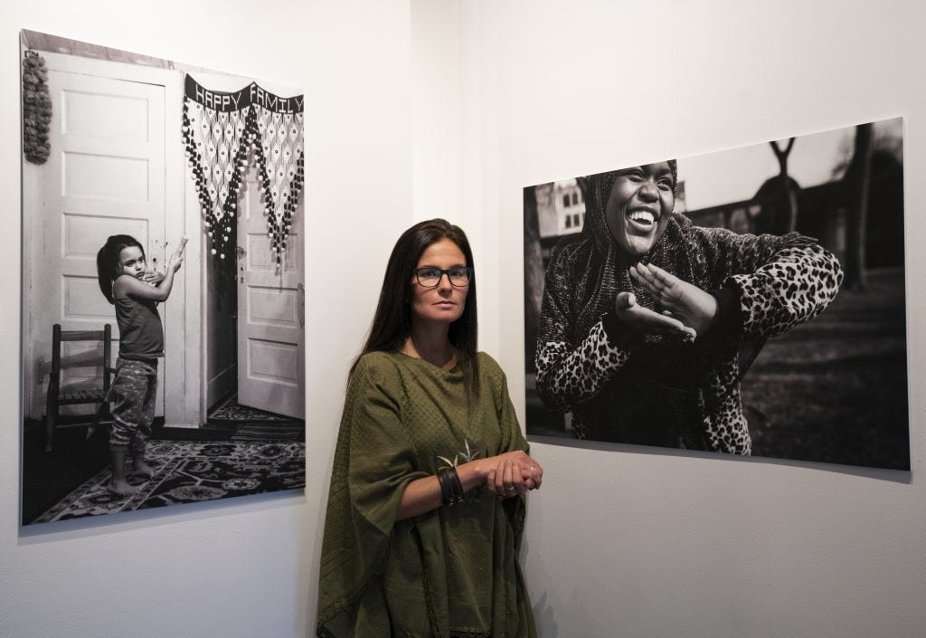 Maranie Staab, photographer, stands in her exhibit in Art Rage gallery in Syracuse, NY.