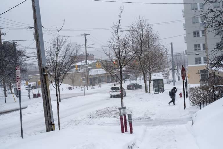 Syracuse University canceled Friday clases as more than a foot of snow was burying Syracuse.