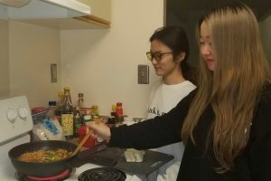 Lubeini Yang and Suyun Chen cook in their south campus apartment