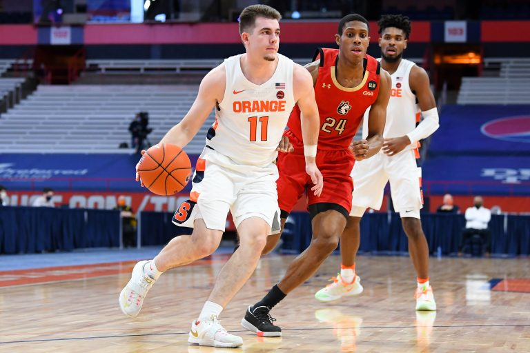 Dec 16, 2020; Syracuse, New York, USA; Syracuse Orange guard Joseph Girard III (11) drives to the basket past Northeastern Huskies guard Shaquille Walters (24) during the first half at the Carrier Dome. Mandatory Credit: Rich Barnes-USA TODAY Sports