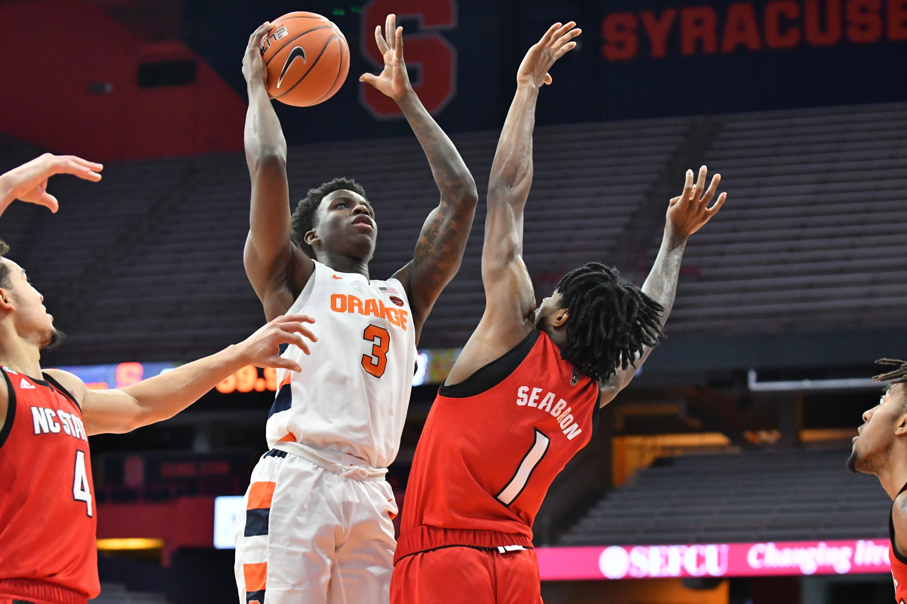 Jan 31, 2021; Syracuse, New York, USA; Syracuse Orange forward Kadary Richmond (3) shoots the ball as North Carolina State Wolfpack guard Dereon Seabron (1) defends in the first half at the Carrier Dome. Mandatory Credit: Mark Konezny-USA TODAY Sports