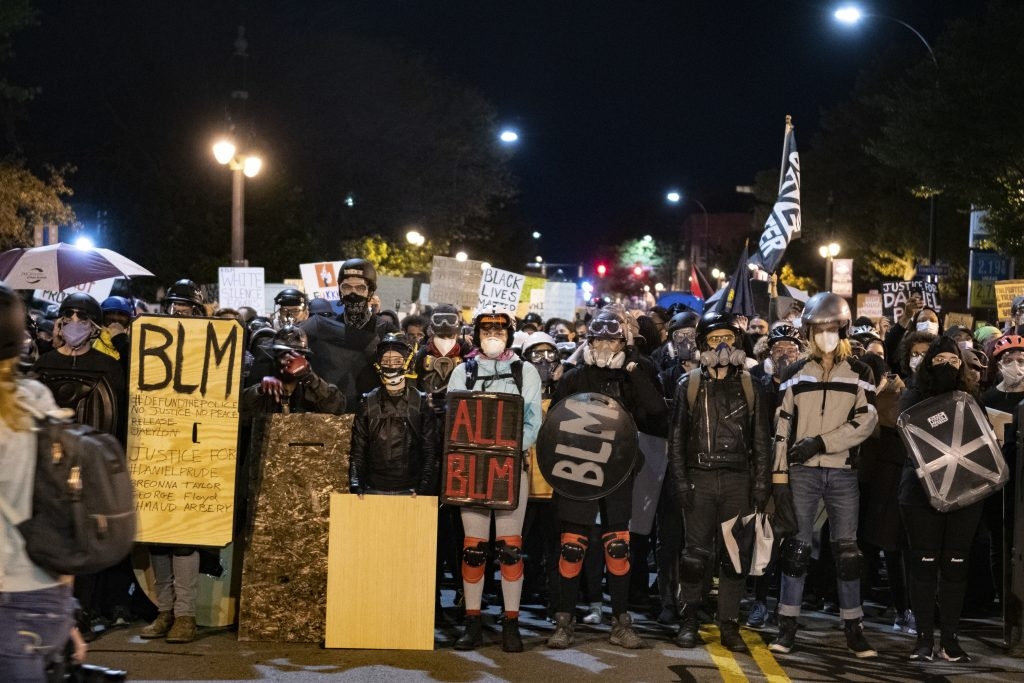 Protesters form a wall as they march to Exchange Boulevard. Demonstrators were equipped with homemade shields, goggles and masks in preparation.