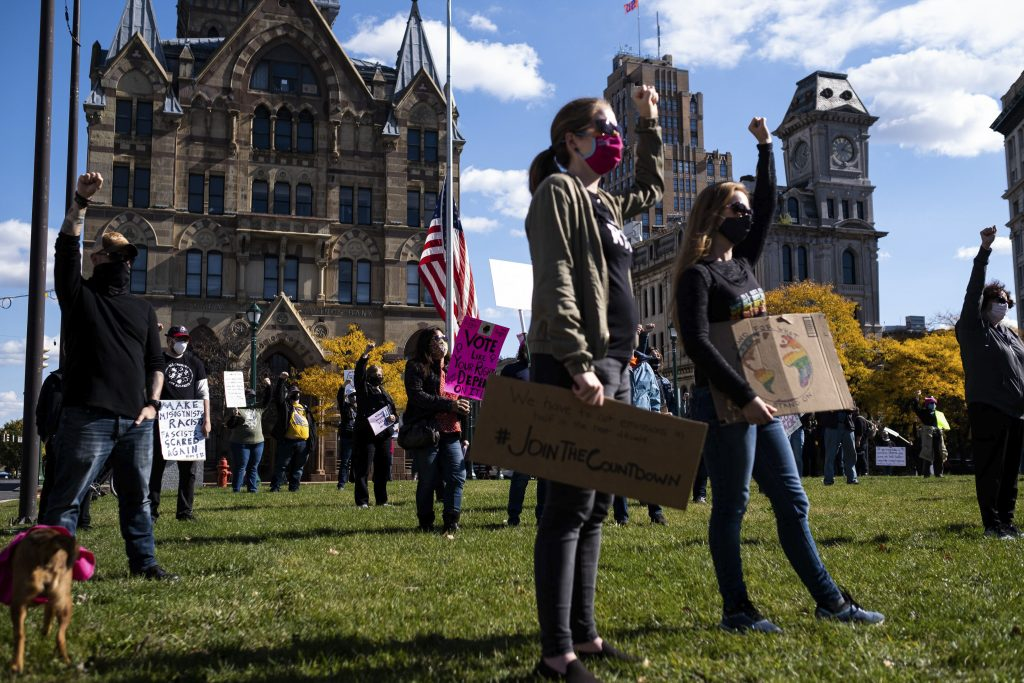 Supporters raise their fists in solidarity with the speakers at an Oct. 17, 2020, women's rights rally