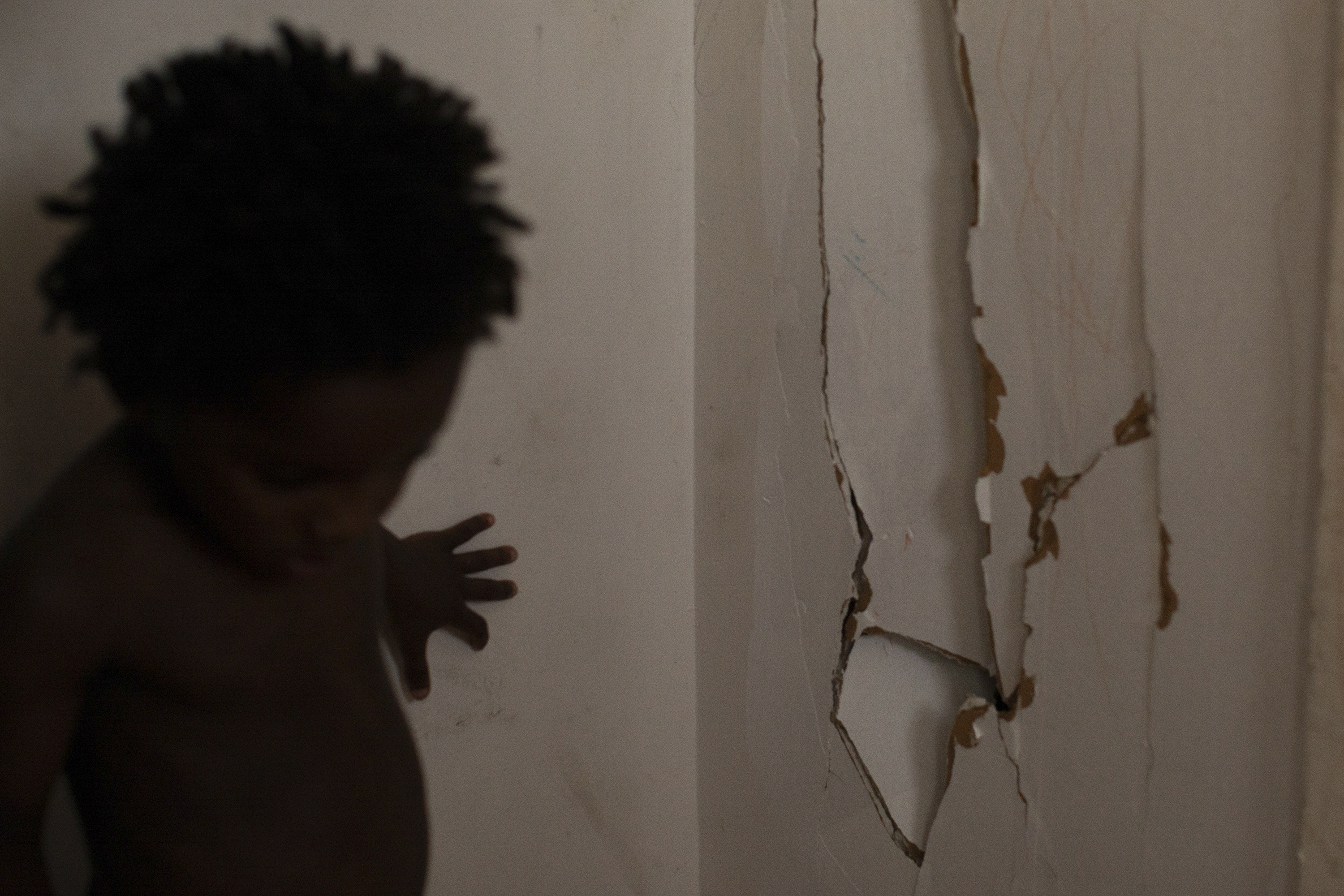 Darlene touches a broken wall that split when her three-year-old twins were playing against it.