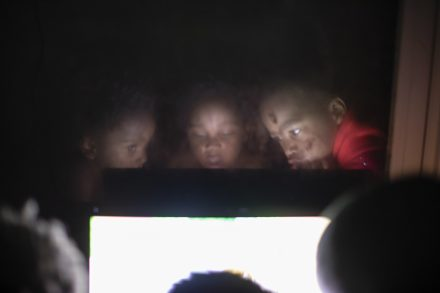 Rashad, Devon, and Azari spend the night watching their favorite cartoons hanging off a dresser where the television is located as Darlene prepares them dinner.