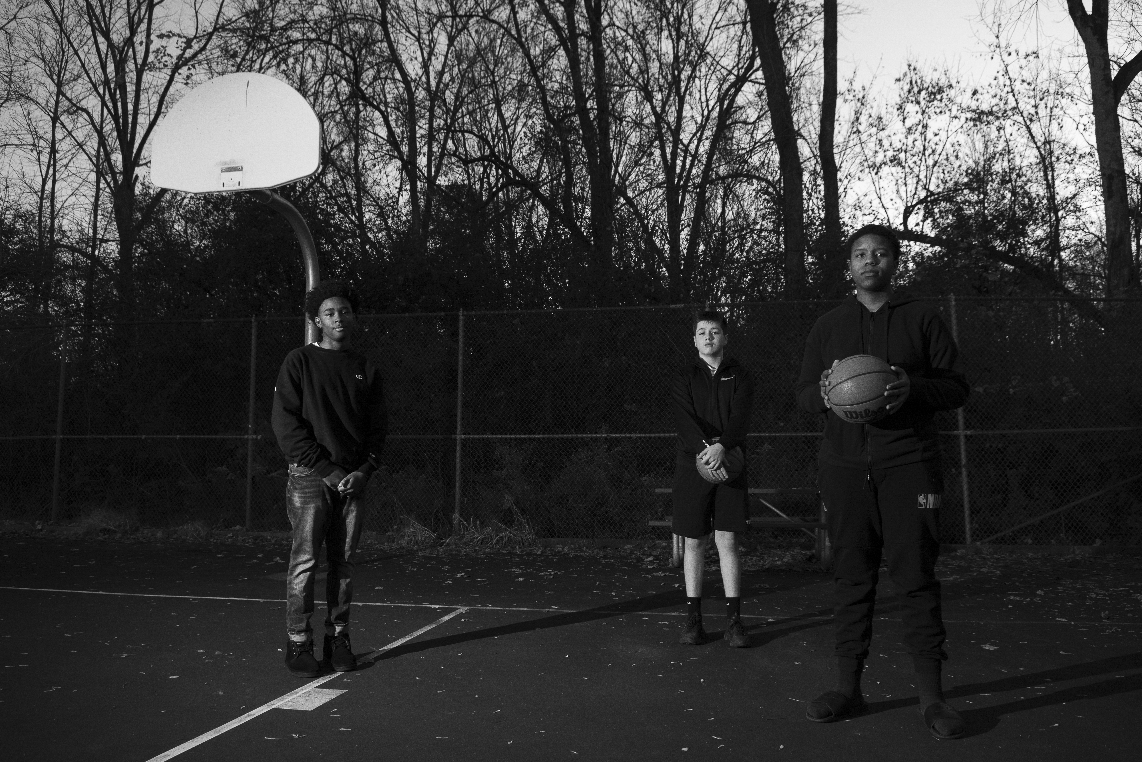 Jamir Ellerby, Jay Peña and Brian Hall stand under the rimless basketball hoops in Syracuse's Kelley Brothers Memorial Park.