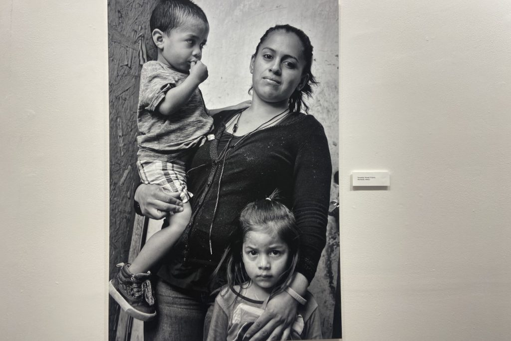 Woman with her toddler-age son on her right hip and her left hand draped over her small daughter holding her close. All looking at the camera.