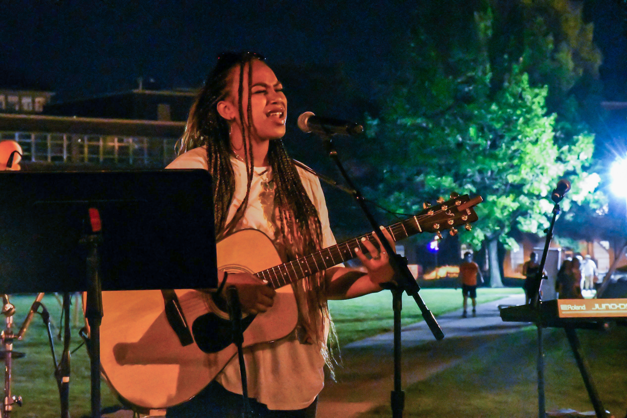 BRI singing and playing her acoustic guitar at the One with the Concert on the Orange Grove