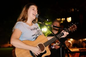 Sarah Gross singing and holding her acoustic guitar a the One with a Concert on the Orange Grove concert