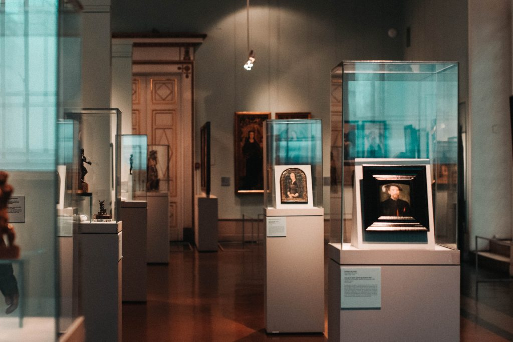 Art pieces is display cases in a gallery
