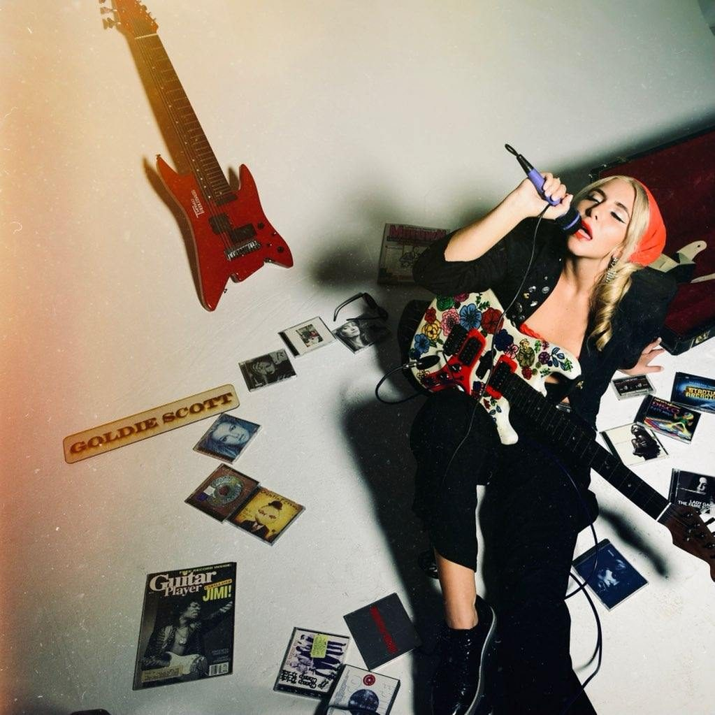 Goldie Scott singing into a microphone surrounded by CDs and guitars