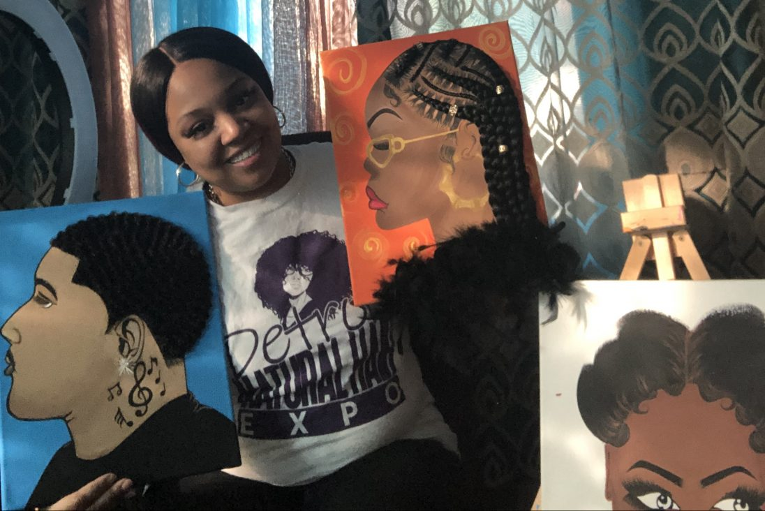Hairdresser and artist Tiffany Moore posing with some of the paintings she has created