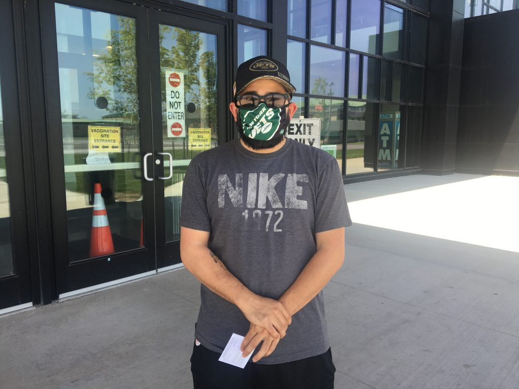 Paul Esden stands outside a vaccination center.