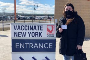 Leah Dunne holds her vaccination card after receiving her first dose of the COVID-19 vaccine at the New York State Fairgrounds.