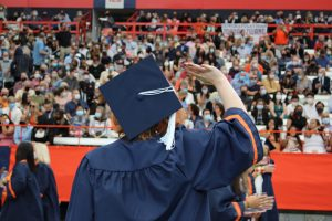 A 2020 SU graduate waves before the September 19, 2021 Commencement ceremony in the Dome on September 17th, 2021.