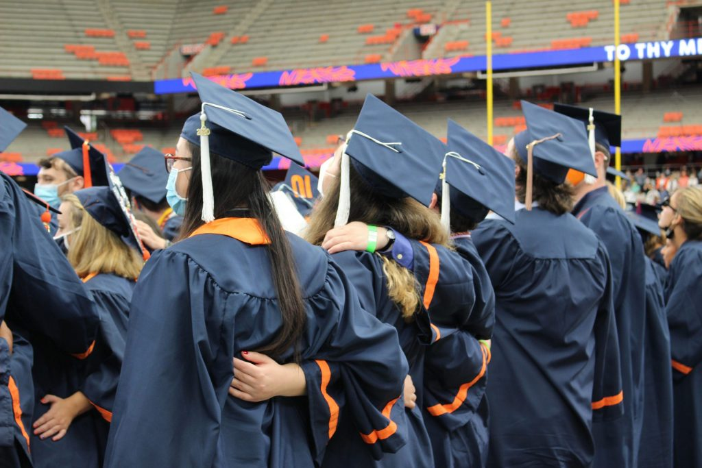 2020 SU graduates share a moment during the September 19, 2021 Commencement ceremony in the Dome.