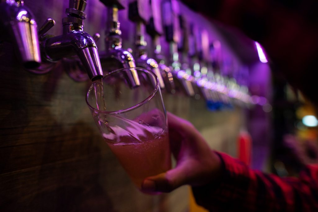 A bartender at Buried Acorn Brewing pours a glass from a tap on September 10th, 2021.
