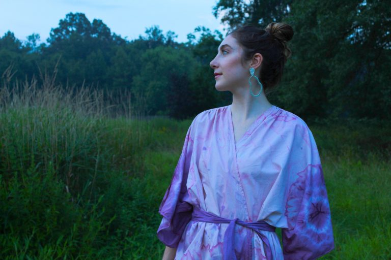 A model in a green field wears a kimono designed and made by Isabelle Collins. She used recycled cotton sheets and then tie-dyed them using beets and blueberries.
