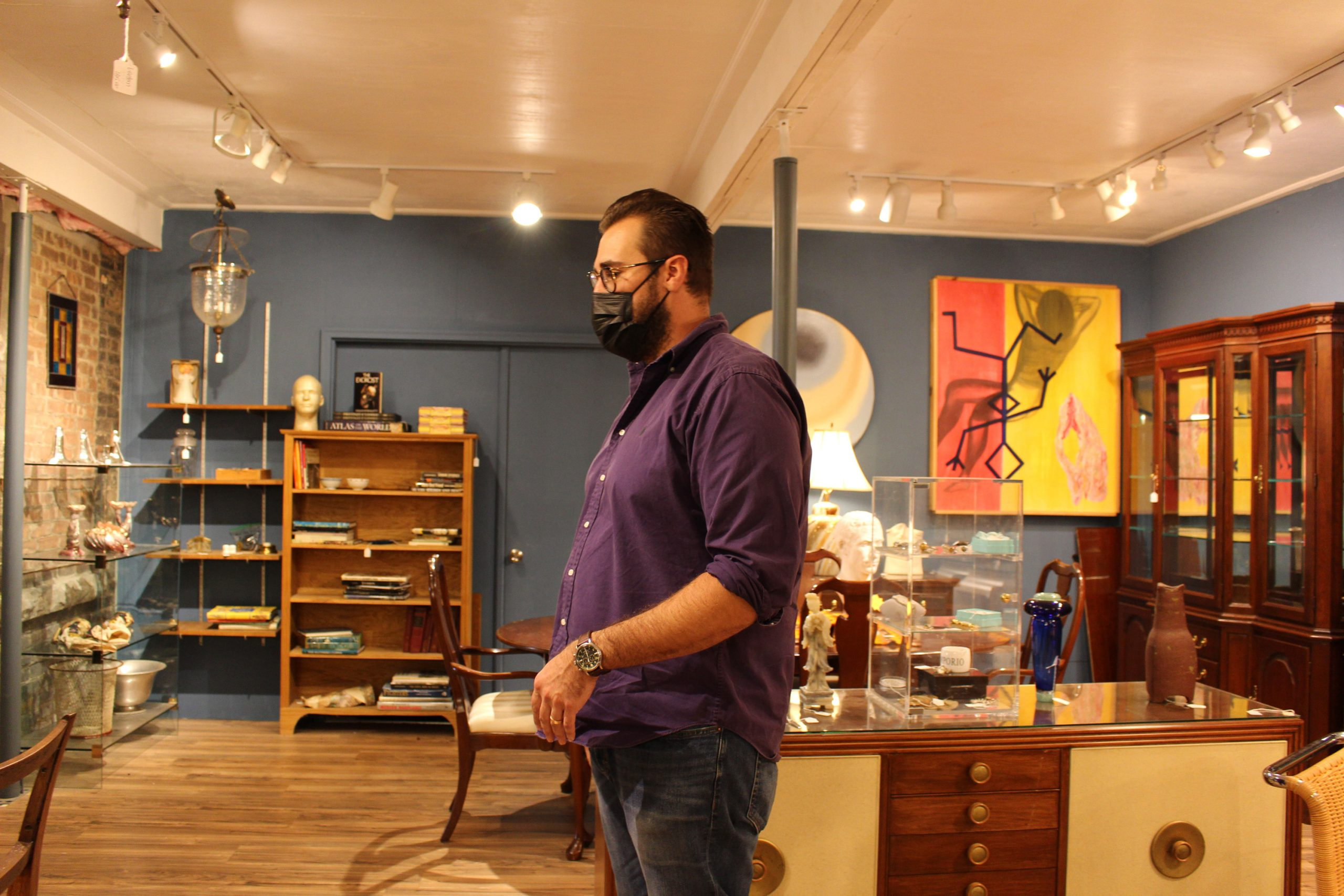 Syracuse Antiques Exchange co-owner Matt Pastore stands among furniture in the store