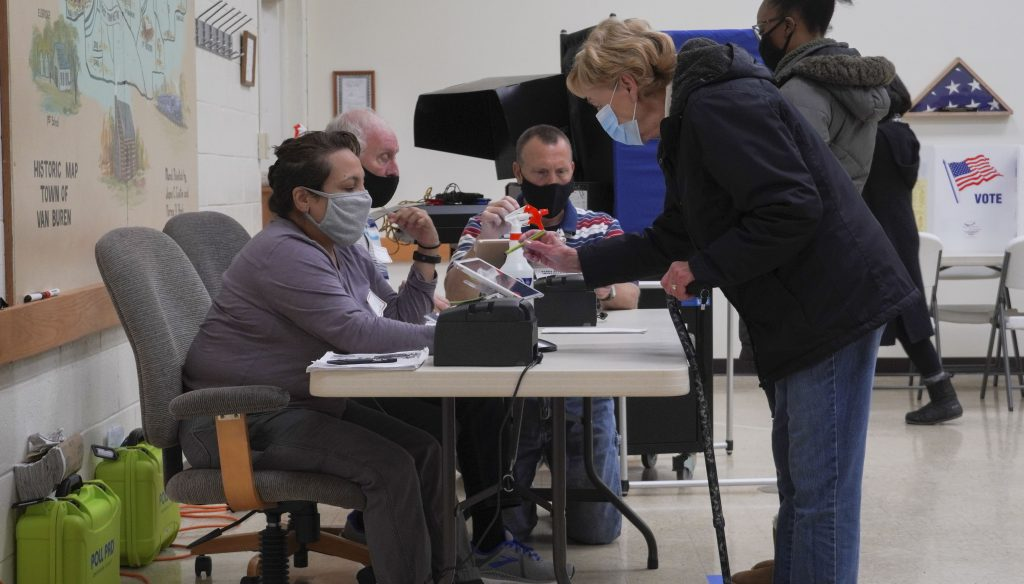 Paul Wiedeman, center, the poll site manager, works with a poll worker and a voter to get them thier ballot. This was the first election Wiedeman has been a poll site manager, but he has worked the polls in past cycles. (Photo by Patrick Linehan)