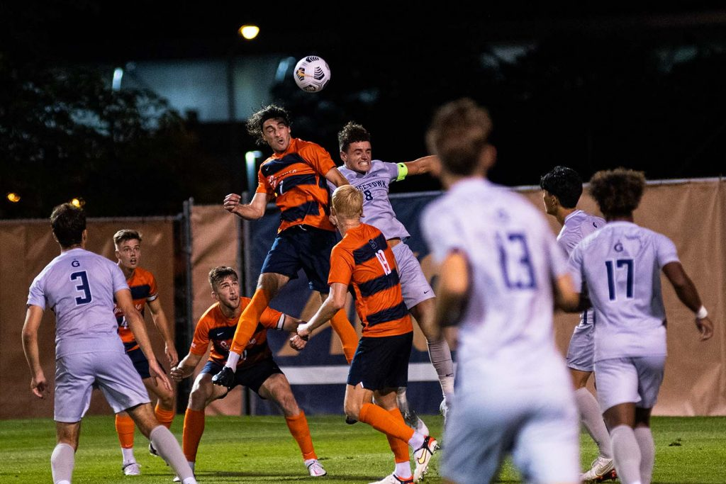 A member of the Syracuse Men's Soccer team leaps for a header versus Georgetown.