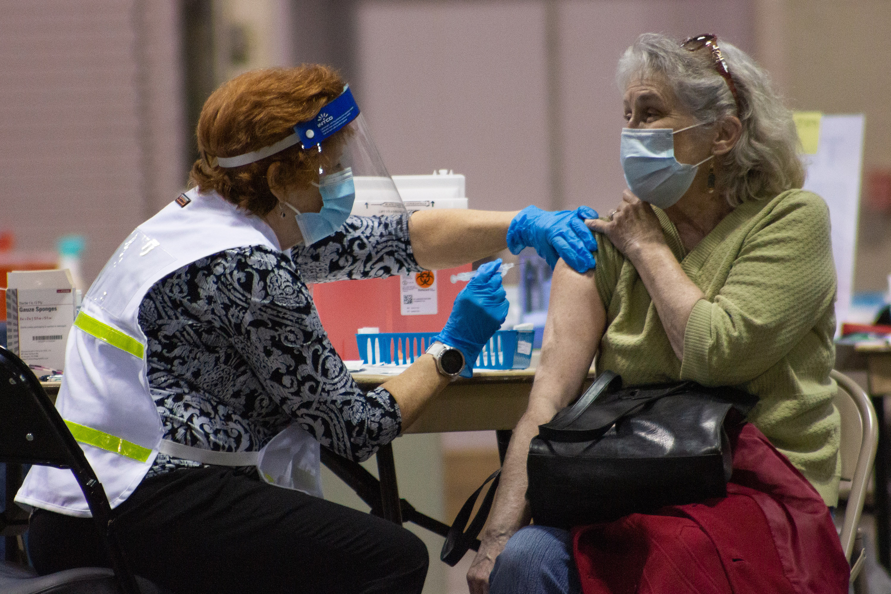 A woman receives a dose of the COVID-19 vaccine from a volunteer nurse.