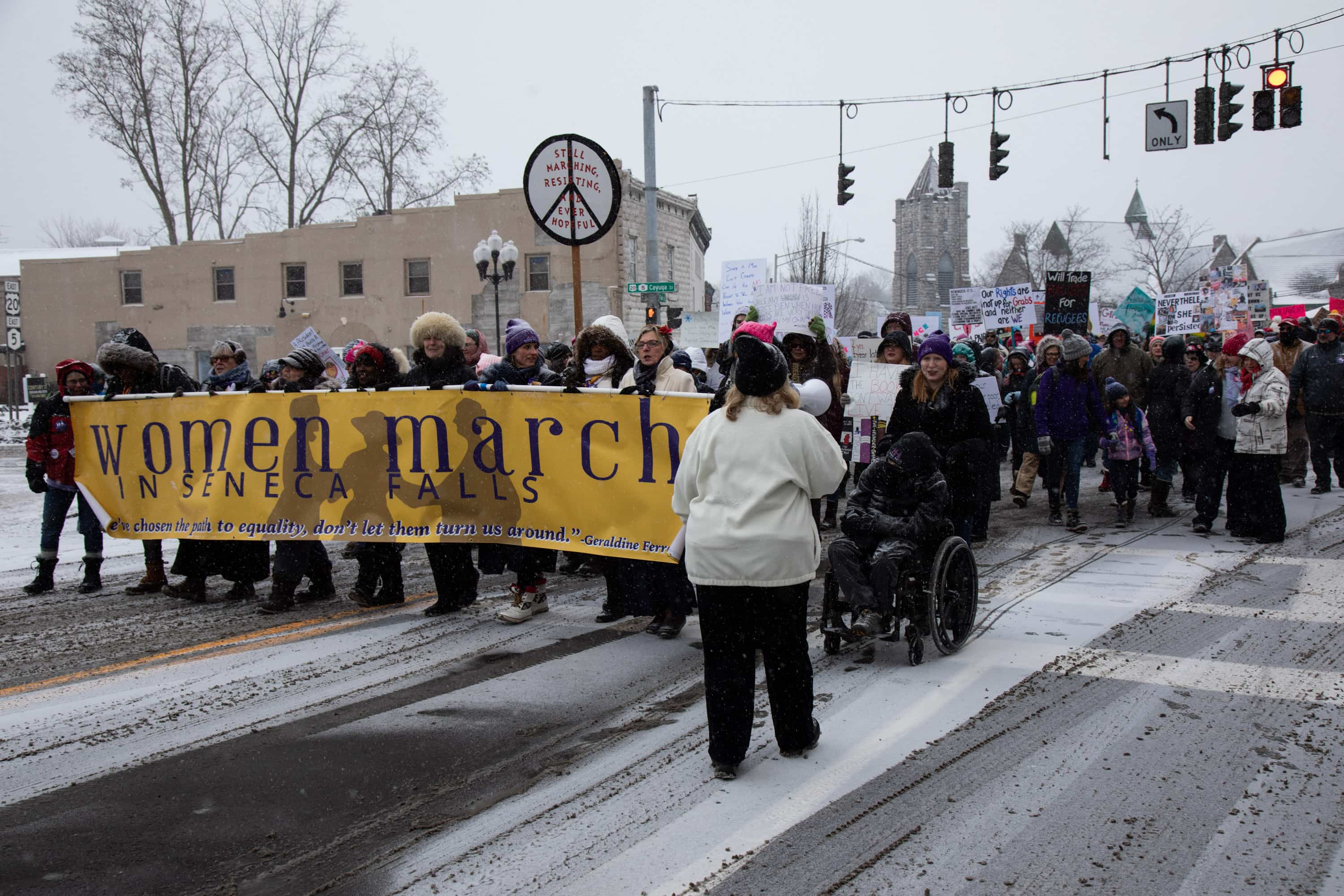 Activists including Leader of Ceremonies, Maureen Quigley; Colleen Kattau, Rev Leah Ntuala Pastor; Diana Smith, Mayor of Seneca Falls (former); Suffragist Descendents, Coline Jenkins and Elisa Kellogg Shaffer; Gwen Webber-McLeod, CEO, Gwen, Inc; Sally Roesch Wagner, author and Matilda Joslyn Gage Center, Executive Director lead the Women's March from Trinity Park in Seneca Falls this morning, Saturday, January 19th.