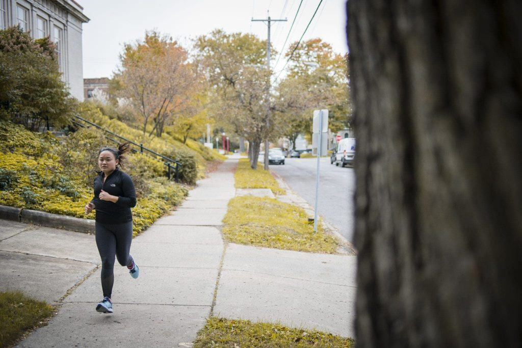 Syracuse University student Ellie Coggins jogs along Euclid Avenue in Syracuse, N.Y.
