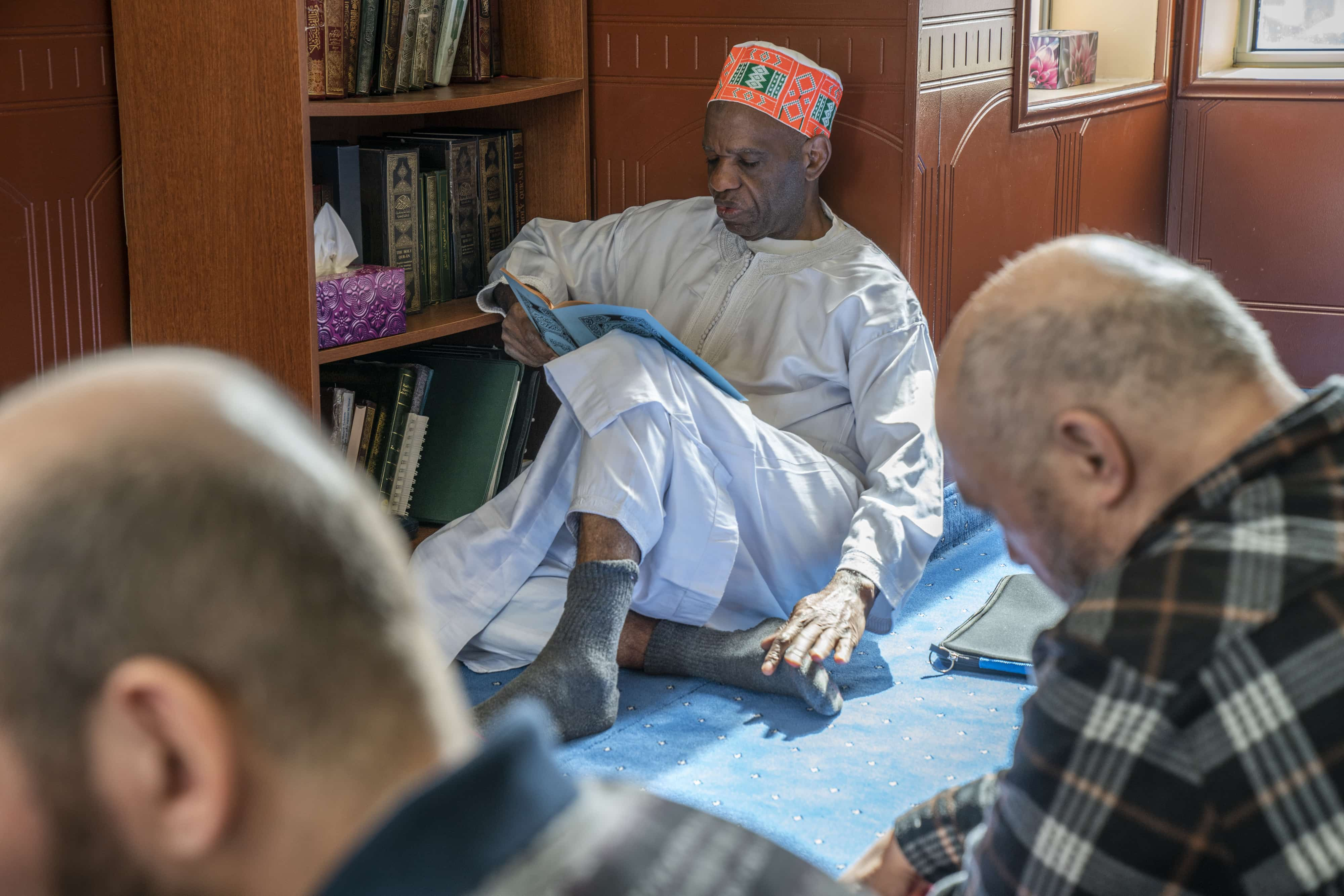 A man studies the Quran amidst the congregation. The Quran is the main holy scripture of Islam.