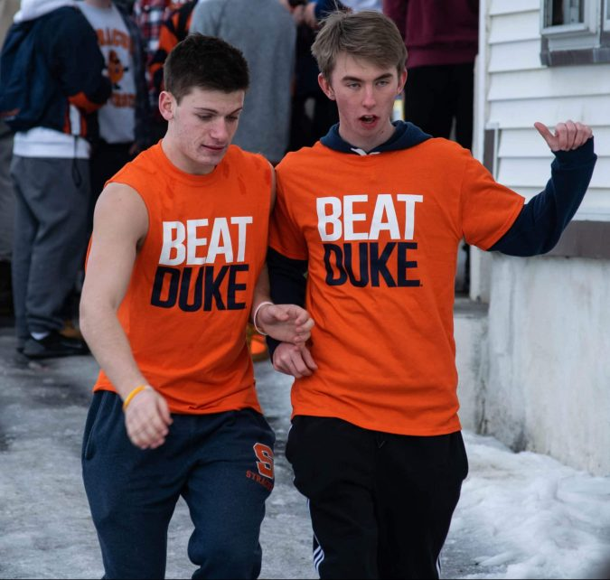Sean Manzella, Broadcast and Digital Journalism freshman (left), and Alex French, University of Connecticut freshman (right), slide down the icy driveway after leaving a pre-game party along University Avenue.