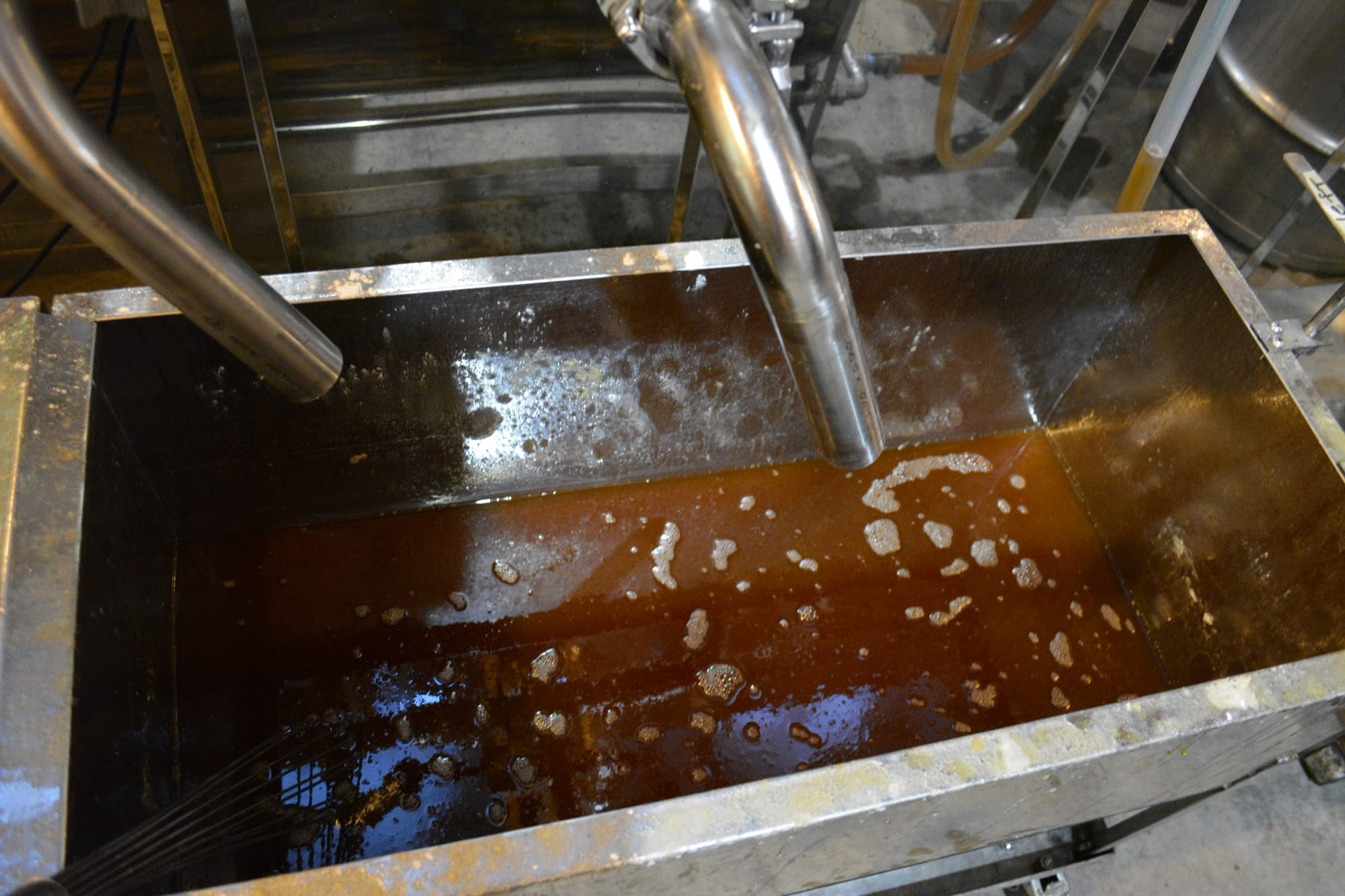 The piping hot syrup then flows out a spout and into a metal trough.