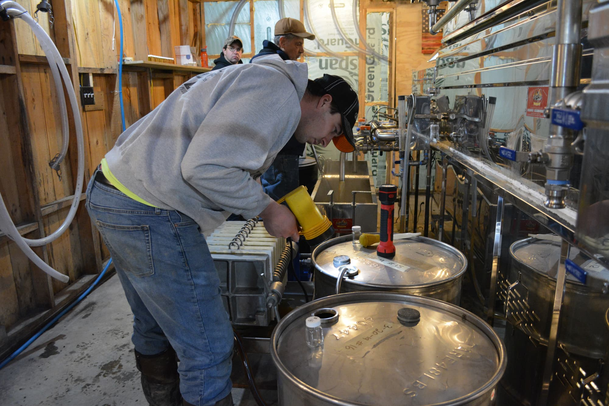 The finished syrup courses through a final set of tubes and into 40-gallon drums. To ensure the barrels don't overflow, Williams monitors the syrup's level with a flashlight.
