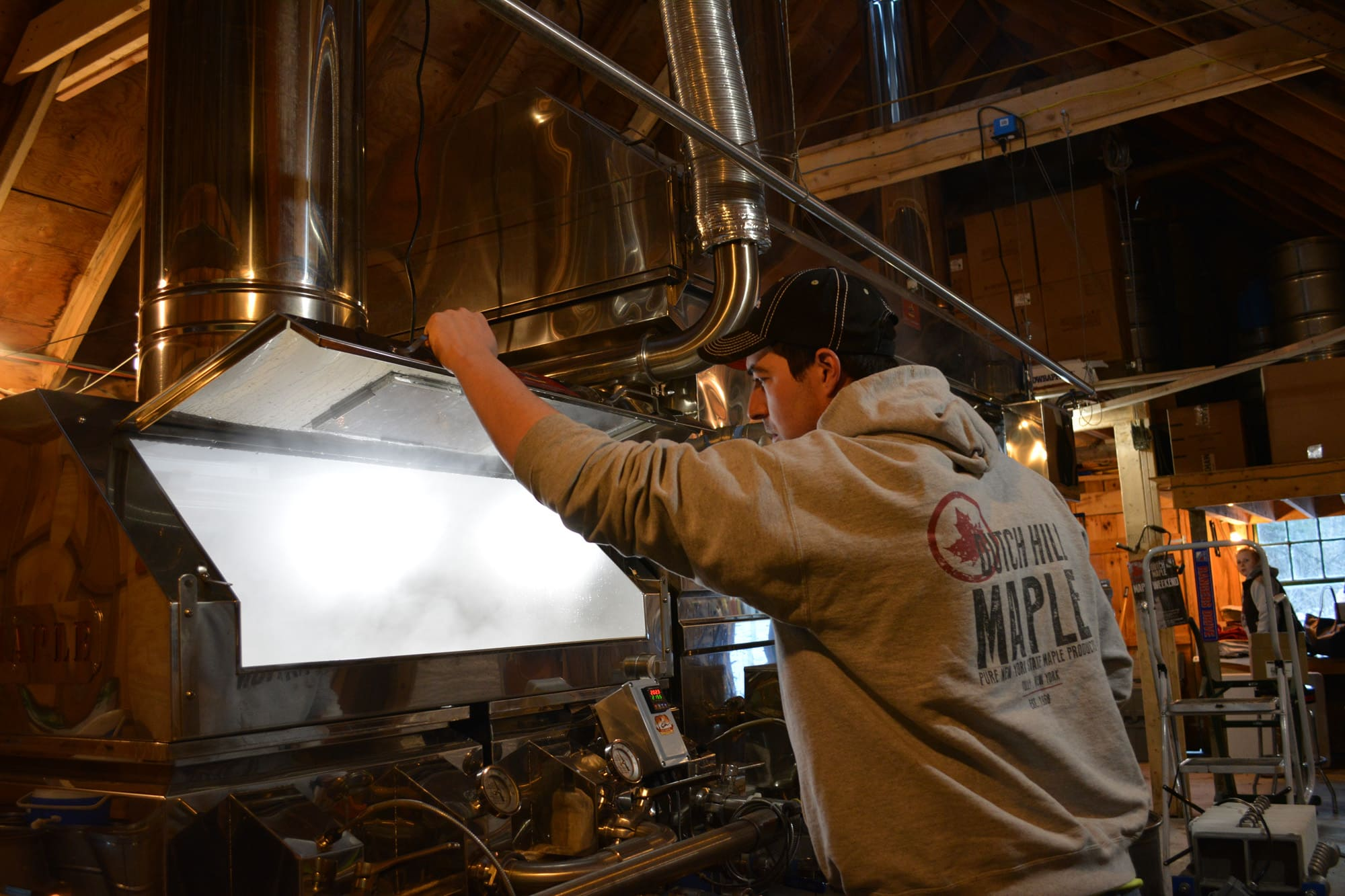 As the sap moves through the evaporator, Nate Williams of Dutch Hill opens the window to check the boiling sap for foam, which is caused by minerals and bacteria. If foam appears, Williams adds a defoaming agent to the machine.