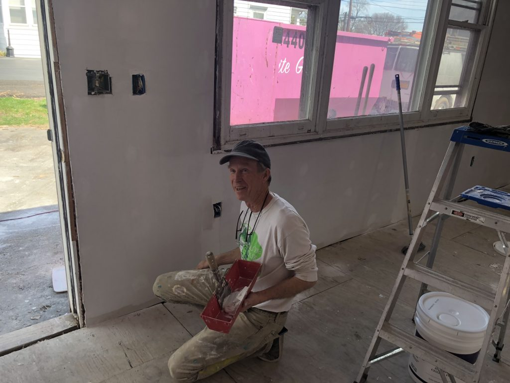 Patrick Coyne paints inside the house at 108 Onondaga Avenue that Paul Finch is restoring in spring 2019.