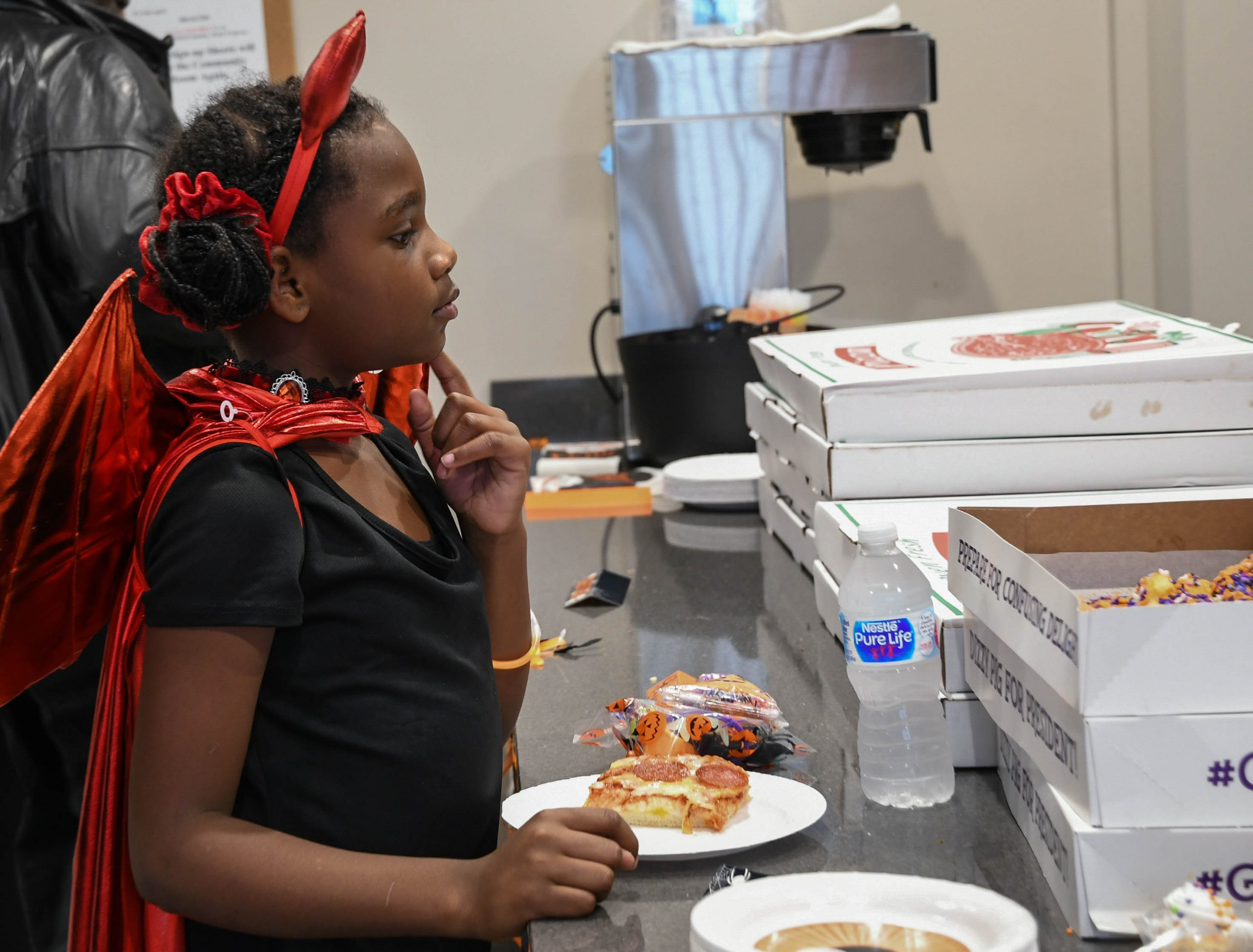 Amarionna Brown contemplates which donut to choose at Clinton Plaza's Halloween party on October 31, 2019.