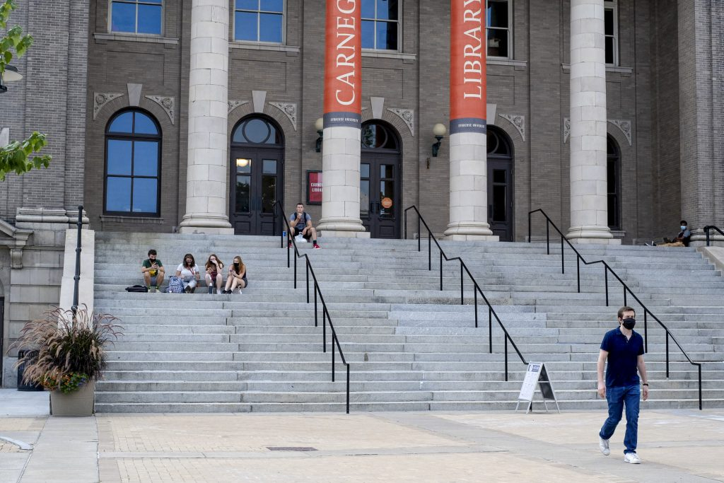 Small groups of students hang out on the steps of Carnegie Library on the first day of the fall semester.