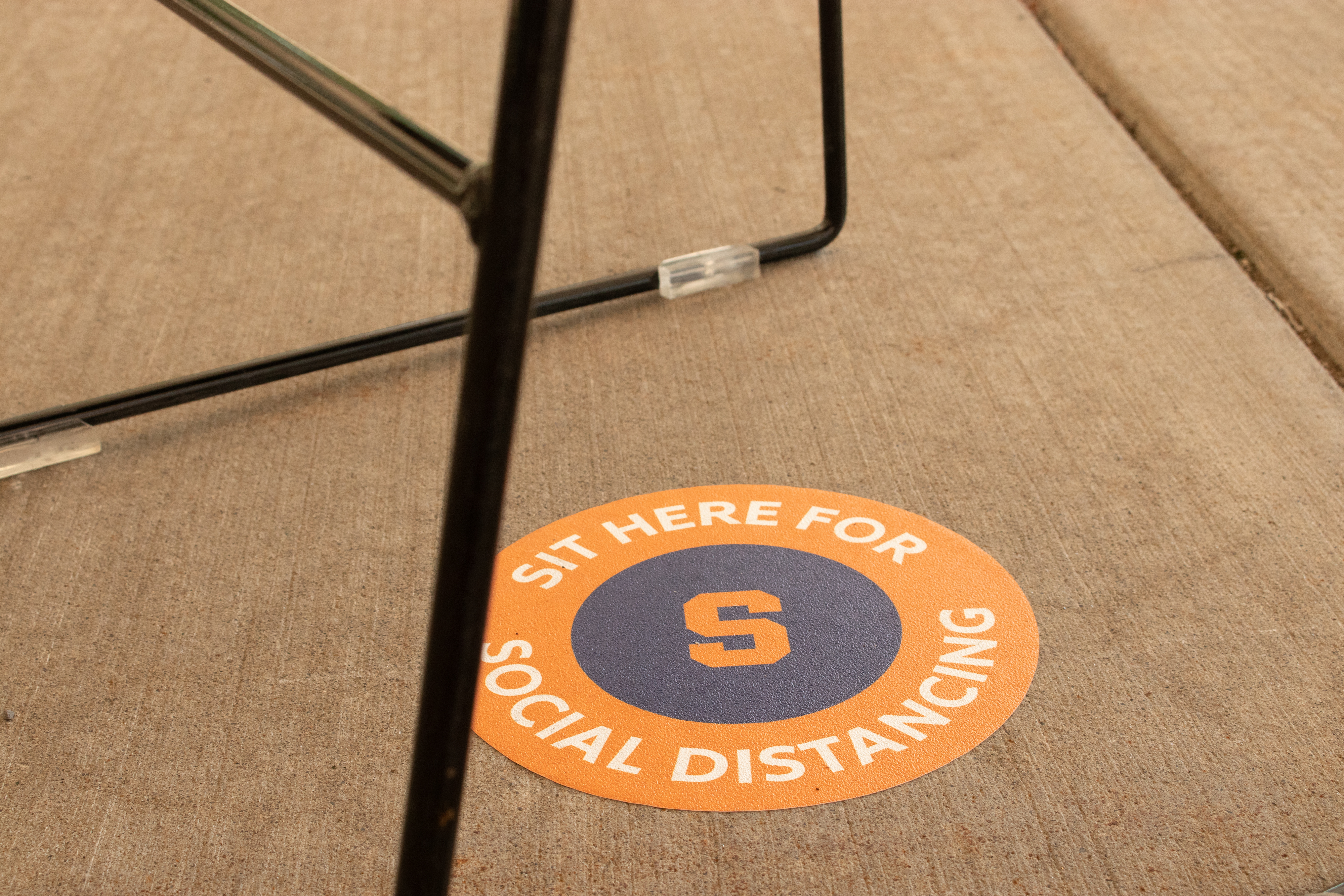 Signs designate social distancing safe locations on Syracuse University's campus.