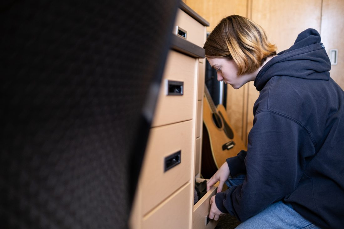 Emily Burris looks in her drawers for clothes to pack to take home.