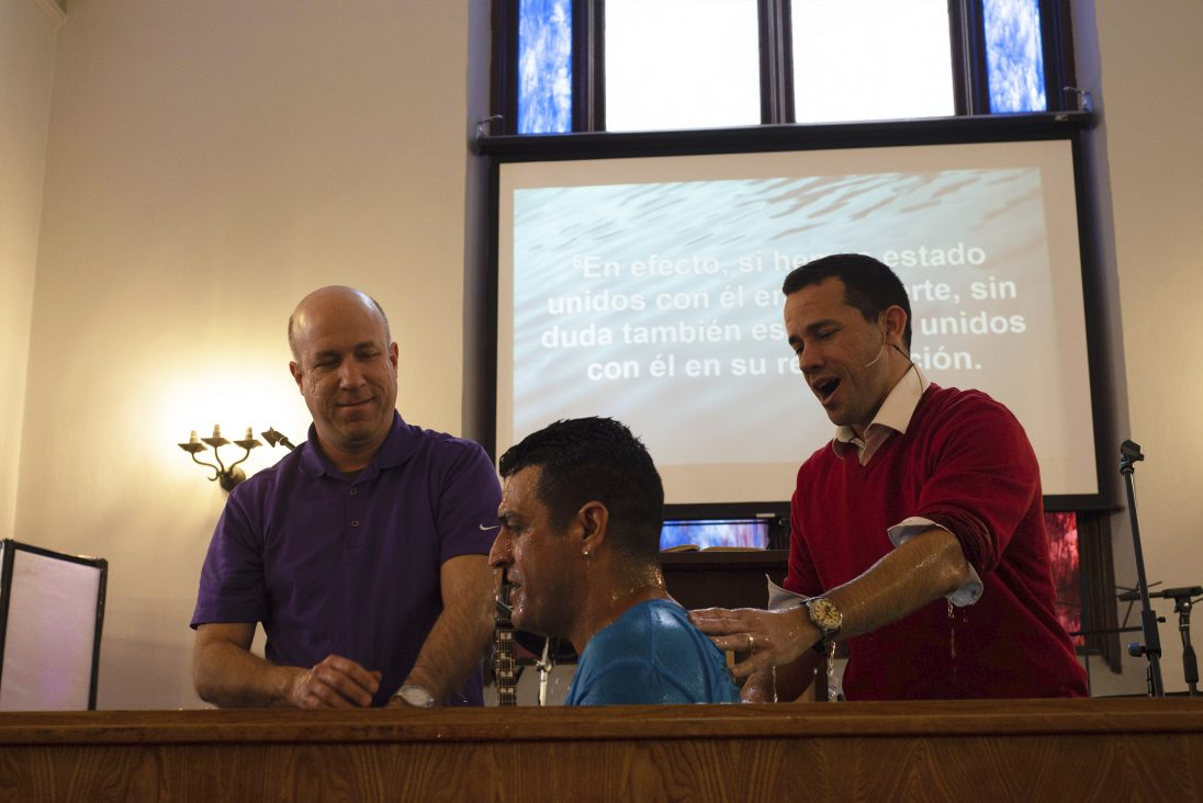 Pastor Reynier Martinez (right), baptizes member of the congregation