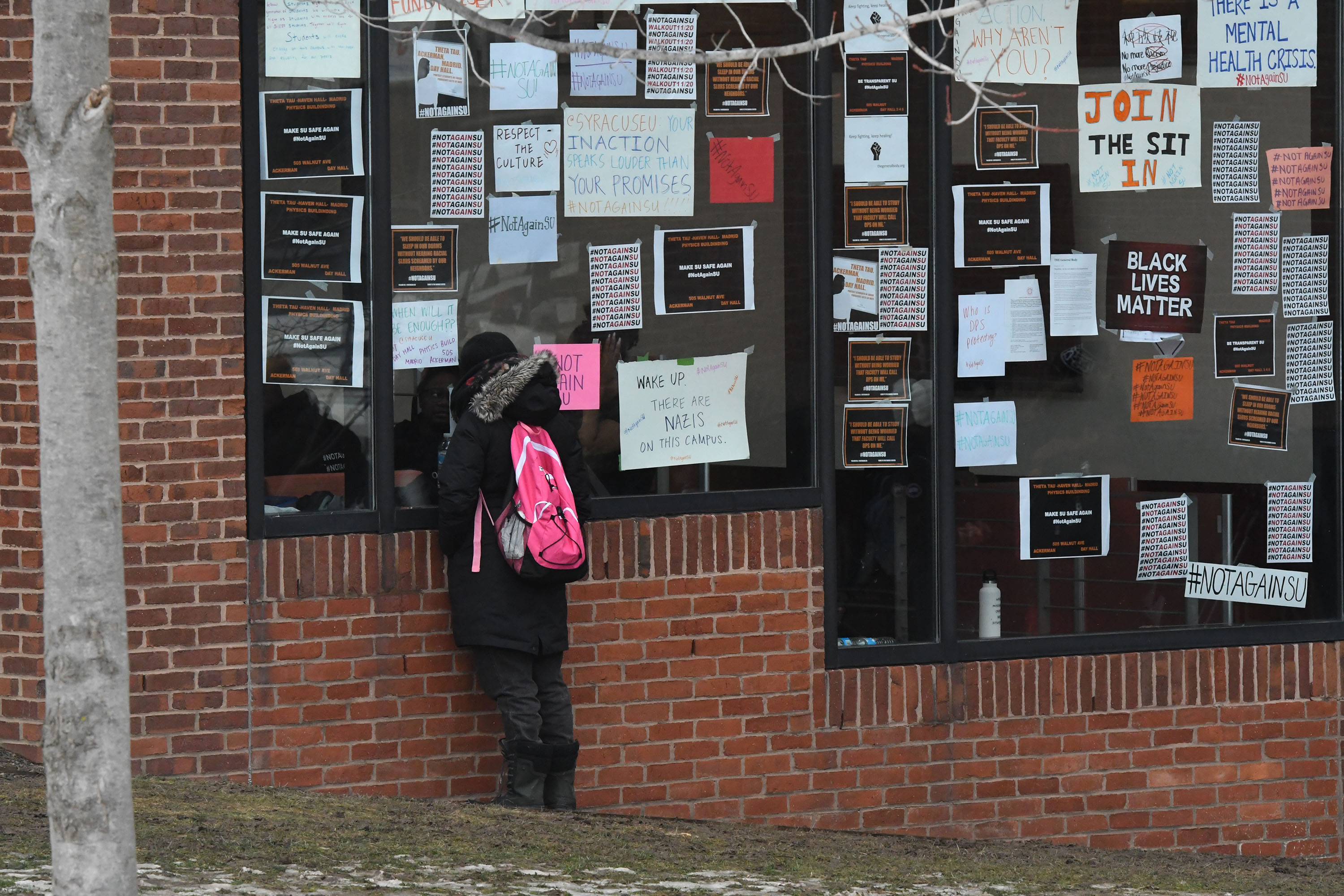 A student presses up against a window of Crouse-Hinds Hall to speak to a friend inside.