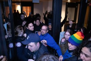 DPS campus security and Syracuse University administrative faculty attempt to hold protesters back as they attempt to push into Crouse Hinds Hall on the night of February 18, 2020.
