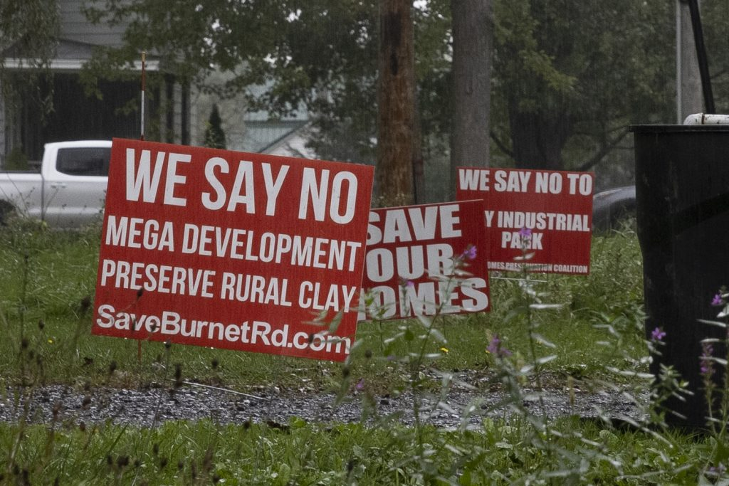 Bright red signs are displayed on the lawns of multiple homes on Burnet Road in Clay.