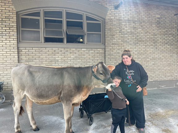 Miranda Bango waits with her son and his cow, Lollipop, outside of the youth dairy judging contest at the New York State Fairgrounds.