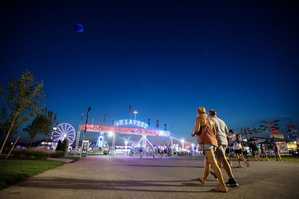 A pair of fairgoers walk toward Midway at the New York State Fair.