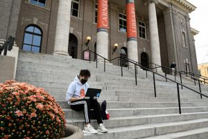 Student works online on the steps of Carnegie Hall.