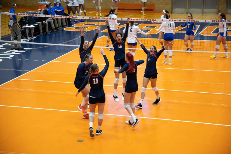 The Syracuse volleyball team celebrates after scoring a point against Pitt during their three-set win on Saturday.