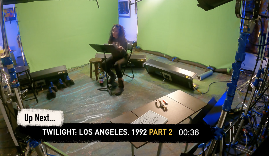 "A behind the scenes look as Patrese McClain performs in ""Twilight: Los Angeles 1992"" in front of the green screen of Syracuse Stage."