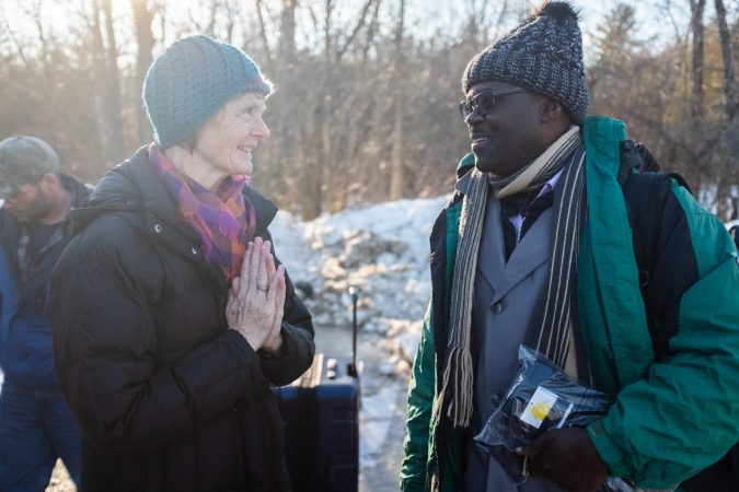 Janet McFetridge, the mayor of Champlain, NY and an immigration activist who visits Roxham Road several times a week, greets a Ugandan man as he arrives at Roxham Road and prepares to cross into Canada.