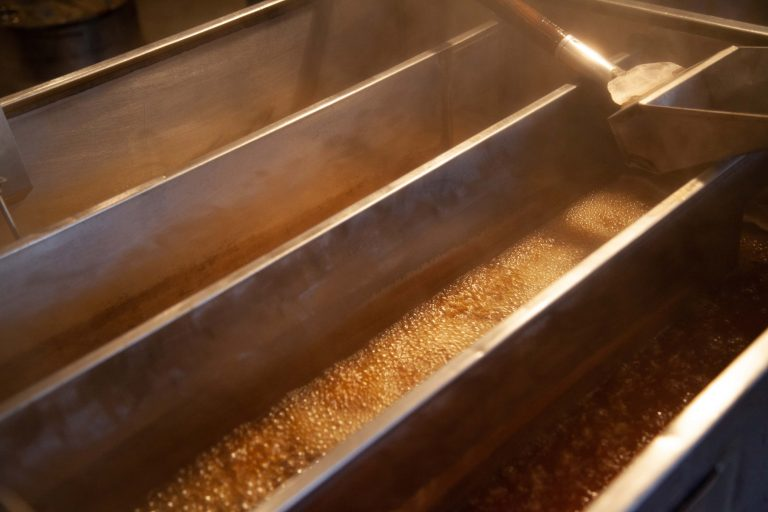 Maple syrup collects in vats at a farm.